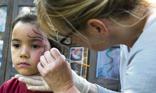 A child sits to have her face painted during the Ramstein and Vogelweh Community Center's Olympic Family Night Aug. 22, 2016, at Ramstein Air Base. Along with face painting, children were able to compete in six events to receive a medal.