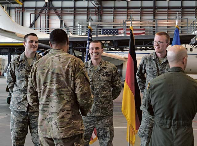 Photo by Senior Airman Nesha Humes  Airmen talk after a coin ceremony Aug. 10, 2016, on Ramstein Air Base. Master Sgt. James McConaghay, U.S. Air Forces in Europe directorate contingency manager, Tech Sgt. David Hobeck, 86th Maintenance Squadron unit deployment manager, Tech Sgt. Austin Schierberg, 86th MXS repair and reclamation craftsman, Staff Sgt. Cory Garland, 86th MXS repair and reclamation journeyman and Staff Sgt. Geoffrey Brew, 86th MXS UDM, were recognized for successful completion of an aircraft recovery mission.