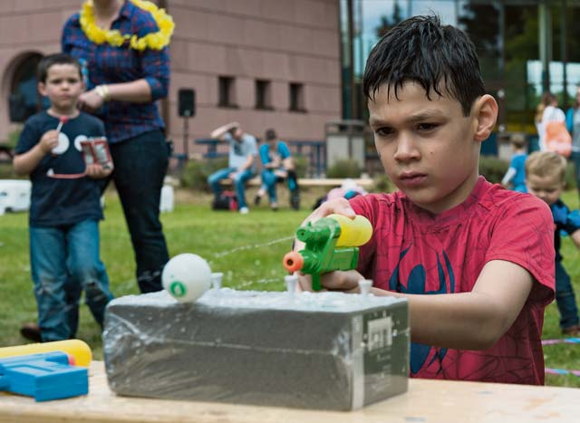 Photo by Airman 1st Class Lane T. Plummer  A child squirts a ping pong ball with a water gun during a party for families of deployed Airmen Aug. 12, 2016, at Ramstein Air Base.