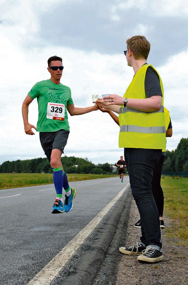 A volunteer hands a water cup to a participant during the Ramstein Half Marathon August 20, 2016, at Ramstein Air Base. Water stations passed out cut fruit and water approximately every two miles to refuel the runners during the race.