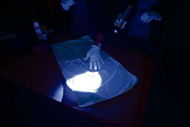 Air Force Office of Special Investigation 13th Field Investigations Squadron agents demonstrate a DNA sample search on a towel Aug. 11, 2016, at Ramstein Air Base. There are three fields of operations at the AFOSI: criminal investigation, fraud investigation and counter-intelligence investigation.