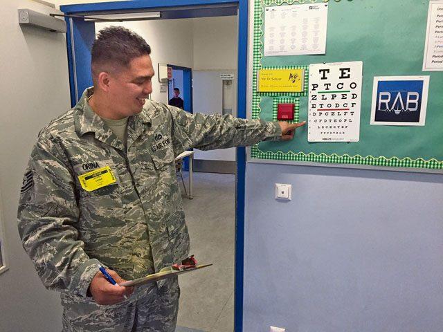 Tech. Sgt. Jeffrey Orina, U.S. Air Forces in Europe Civil Engineering, assists students with the eyesight portion of the health screening Sept. 19 at Ramstein Middle School.
