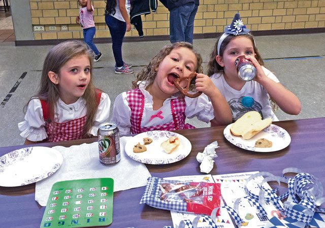"Analise Gaunt (left), Lexi Barnes (center) and Ava Martin take a break from bingo to eat snacks during ""Oktoberfest Family Bingo Night"" Sept. 30 at Vogelweh Elementary School. Over 100 VES families came out for the school's first ""Oktoberfest Family Bingo Night"" as part of a Parent Teacher Student Association fundraiser."