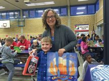 "Sean Richesson poses for a photo with his mother Brenda Richesson after winning an electronic book reader at ""Oktoberfest Family Bingo Night"" Sept. 30 at Vogelweh Elementary School. Each game had two winners, a child and an adult. Prizes included German steins, electronic book readers and digital cameras."