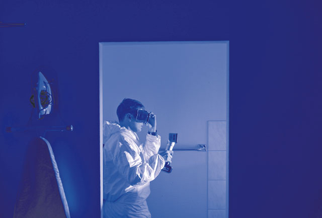 An Air Force Office of Special Investigations 4th Field Investigations Squadron agent utilizes an alternate light source during a mock crime scene Oct. 6 on Ramstein. Agents utilize light sources to search for biological fluids undetectable to the naked eye. The 4 FIS tests units within U.S. Air Forces in Europe in order to assess agents' techniques and readiness.