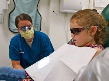 "Capt. Heather Rybar, 86th Dental Squadron general dentist, talks to her patient, Emma LeNeave, during the 86th Dental Squadron's ""Little Teeth, Big Smiles"" event Nov. 5 on Ramstein. The event invited parents to bring their children, up to 10 years old, in to receive a dental checkup and cleaning."