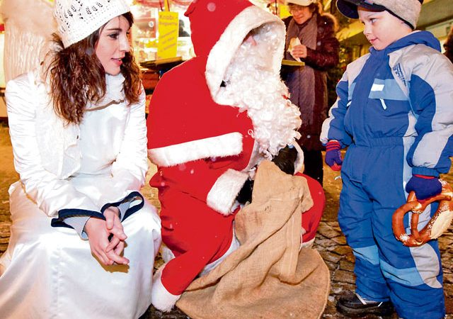 """Photo courtesy of the City of Kaiserslautern Santa Claus comes to pass out goodies to children Dec. 6 at the Christmas market in Kaiserslautern. Germans observe """"Nikolaustag,"""" or """"Santa Claus Day,"""" every year on Dec. 6."""
