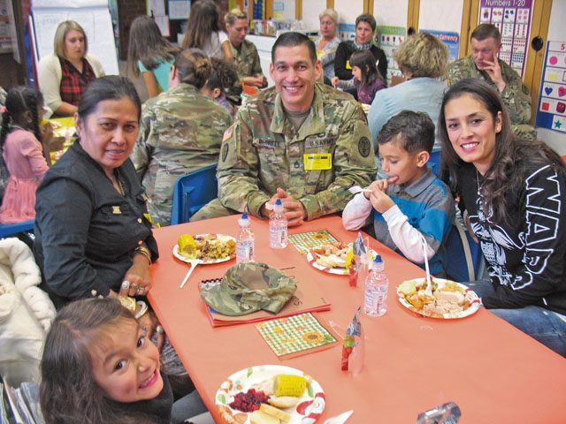 Kallum Ferrell and his family enjoy a Thanksgiving Feast Nov. 22 in Julie Wittenberg's first-grade class at Landstuhl Elementary Middle School. Before everyone ate, the students read and presented a pilgrim book to their families that they made that month.