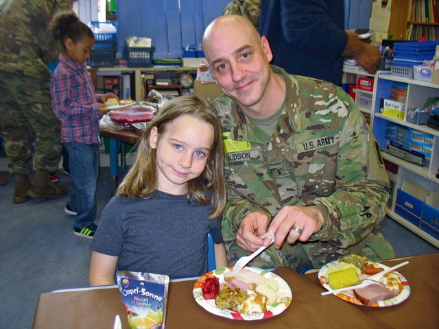 Parker Hudson and his dad, John Hudson, enjoy a Thanksgiving Feast Nov. 22 in Julie Wittenberg's first-grade class at Landstuhl Elementary Middle School. Before everyone ate, the students read and presented a pilgrim book to their families that they made that month.
