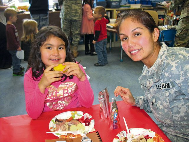 Hailey Soriano and her mom, Victoria Garth, enjoy a Thanksgiving Feast Nov. 22 in Julie Wittenberg's first-grade class at Landstuhl Elementary Middle School. Before everyone ate, the students read and presented a pilgrim book to their families that they made that month.