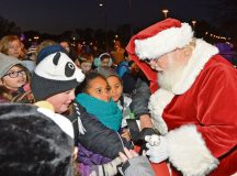 Santa Claus hands out candy to children after a Christmas tree lighting ceremony Nov. 28 on Ramstein. For the ceremony, Santa arrived in a red firetruck instead of the traditional reindeer sleigh.