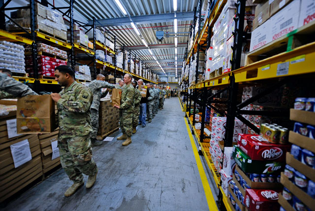 Airmen and Soldiers line up to fill bags with food and supplies at the Thanks for Thanksgiving event Nov. 19 on Vogelweh. KMC leaders banded together to support junior enlisted service members by providing them with all the fixings for a traditional Thanksgiving meal.