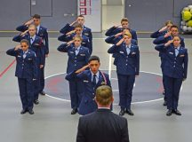 """Wayne Barron, inspector, observes the Kaiserslautern High School second-year cadets demonstrate excellence through a drill demonstration during the Headquarters Air Force Junior ROTC evaluation Oct. 25 at KHS on Vogelweh. The Kaiserslautern High School cadets performed exceptionally well and took great pride in leading and accomplishing their unit briefing, drill demonstration and open ranks inspection. The junior ROTC instructors and cadets earned an overall unit assessment score of """"Exceeds Standards,"""" the highest rating attainable, during the evaluation."""