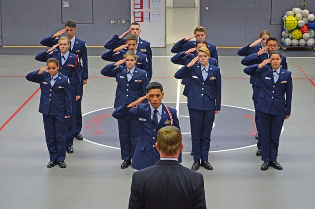 "Wayne Barron, inspector, observes the Kaiserslautern High School second-year cadets demonstrate excellence through a drill demonstration during the Headquarters Air Force Junior ROTC evaluation Oct. 25 at KHS on Vogelweh. The Kaiserslautern High School cadets performed exceptionally well and took great pride in leading and accomplishing their unit briefing, drill demonstration and open ranks inspection. The junior ROTC instructors and cadets earned an overall unit assessment score of ""Exceeds Standards,"" the highest rating attainable, during the evaluation."