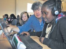 "Sembach Elementary School second- and third-grade students completed ""Hour of Code"" during Computer Science Education Week Dec. 5 through 11 at SES. The objective of Hour of Code is to get more students interested in computer programming, putting them on track to take computer science jobs in the future. Dr. Michael Herrick, Sembach Elementary School educational technologist, helps Nathelyn George during Hour of Code as Samantha Griffiths observes."