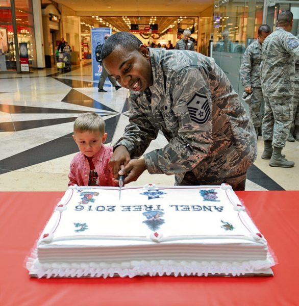 Master Sgt. Timothy Bedford, 21st Operational Weather Squadron first sergeant, and Wyatt Jacobs, son of Chief Master Sgt. Taylor Jacobs, 21st Operational Weather Squadron superintendent, cut a cake at the 2016 Angel Tree ceremony Nov. 8 on Ramstein. Last year more than 200 families received donations, affecting more than 400 children's lives.