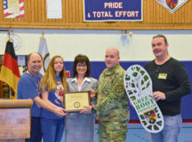 Col. Keith Igyarto, U.S. Army Garrison Rheinland-Pfalz commander (center right), and Konstantin Gross, USAG RP Environmental engineer (far right), present a Green Boot certificate to Sharon O'Donnell, Ramstein High School principal (center); Lauren Jones, RHS Environmental Club president (center left); and Glenn Porter, RHS physical education teacher and Green Boot Program manager, Feb. 15 at RHS. The school chose energy reduction and awareness as its primary focus areas and reduced energy consumption by 0.89 percent, equaling thousands of dollars of savings due to the conscientious use of energy in the 136,805-square-foot school facility.
