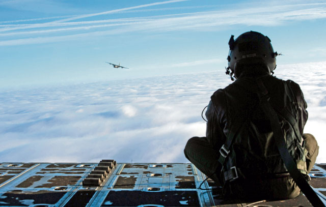 Photo by Senior Airman Lane T. Plummer Airman 1st Class Quinn Harris, 37th Airlift Squadron loadmaster, peers over the skies at another C-130J Super Hercules flying over a blanket of clouds Feb. 10. During the Korean War, the squadron flew airborne assaults at Sukchon, North Korea, and Munsan-ni, South Korea, and aerial transportation between Japan and Korea.