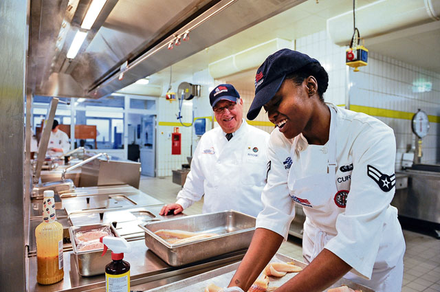 Airman 1st Class Chante Curtis, 786th Force Support Squadron services apprentice, shows Harold Ritchie, Ritchie International principal and hospitality consultant, how she folds fish for presentation during an inspection for the 61st Annual Hennessy Trophy Awards Program Feb 21 at Lindberghof Dining Facility on Kapaun. This is the third year that the 786 FSS has been nominated for the Hennessy award.
