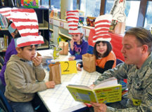 Senior Airman Tyler Allen, U.S. Air Forces in Europe Warrior Prep Center systems administrator, reads to elementary school students during the Dr. Seuss Reading Cafe March 3 on Ramstein. The weeklong event aims to recognize Dr. Seuss' birthday by promoting reading. More than 50 service members volunteered to read a combined 20 hours to the students during the event.
