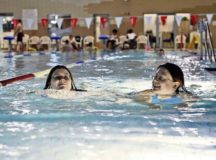 Christina Moore (right), wife of Gary Moore, U.S. Air Forces in Europe visual information specialist, smiles at her daughter Samantha as they swim Feb. 14 at the Aquatic Center on Ramstein. The Biggest Loser challenge has given both women a steady workout plan and diet that they are excited to say feels right for them.