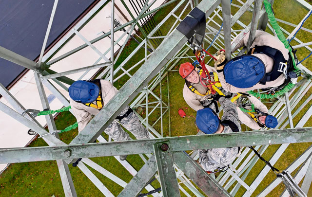 Tech. Sgt. Ryan Joslin, 1st Communications Maintenance Squadron NCO in charge of quality assurance assistance, hangs from an individual descender cable during tower rescue and climbing training March 9 on Ramstein. The 1 CMXS Airmen took turns as a rescuer and simulated victim during the training.