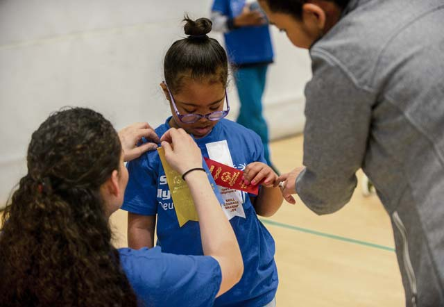 "U.S. Army Sgt. Brenda Contreras, 5th Quartermaster, 21st Special Troops Battalion, 21st Theater Sustainment Command, pins a ribbon on Aviella, a special Olympian, May 19 on Ramstein. Aviella and the other students competing in the 2017 Spring Kaiserslautern Military Community Special Olympics received a volunteer to accompany them as a ""buddy"" throughout the day."