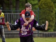 Nick Waller, European Guzzlers softball player, carries James Lucas, Kaiserslautern Middle School student, while running to second base during the Adaptive Sports softball game at Donnelly Park May 4 on Ramstein. The Guzzlers helped the special-needs students during the game as part of the Adaptive Sports program.
