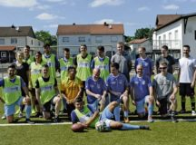 Ramstein Air Base Airmen and Fussballverein Ramstein Fussball Club A-Team pose for a photo during the Grassroots program sports day at FV Olympia Field June 24 in Ramstein-Miesenbach. More than 25 Airmen and soccer players volunteered for the event to help build relations between service members and the local community.