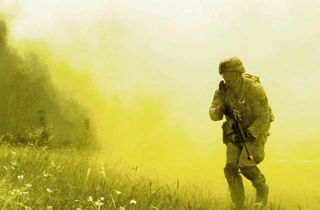 Staff Sgt. Eric Jeffcoat, 100th Security Forces Squadron base defense operation center controller, emerges from smoke grenade smoke during 435 SFS's Ground Combat Readiness Training Center Security Operations Course June 15 at U.S. Army Garrison Baumholder. Conducting missions as a team and being evaluated by the 435 SFS instructor cadre, students showcased knowledge of urban operations, close quarters combat, live firing iterations, mounted and dismounted patrols, entry control point operations, and counter improved-explosive device operations while at Baumholder.