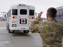 An En-route Patient Staging volunteer helps guide a medical bus on the flightline Oct. 26 on Ramstein Air Base. Patients remain on the bus until accommodations on the plane are ideal for travel.