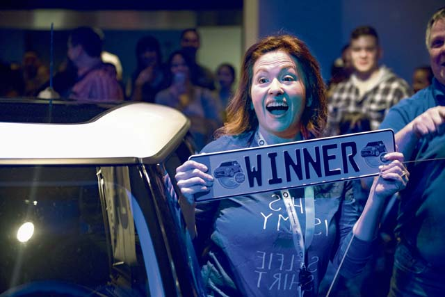 """Yvonne Higby, Vogelweh Elementary School employee, holds a """"winner"""" license plate during the 86th Force Support Squadron's Year of Giving Back Finale Feb. 2 at the Ramstein Enlisted Club. After winning the 2018 Mini Cooper, Higby described the feeling as overwhelming and thanked the 86th FSS for the gift."""