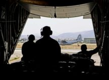 U.S. Air Force loadmasters assigned to the 37th Airlift Squadron, and a C-130J Super Hercules crew chief assigned to the 86th Aircraft Maintenance Squadron sit on the ramp of a C-130J as it taxis down the taxiway after landing May 5 at Elefsis Air Base, Greece.