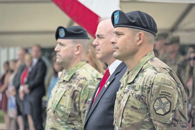 Outgoing garrison commander Col. Keith E. Igyarto (left), Installation Management Command-Europe Director Michael D. Formica and incoming garrison commander Col. Jason T. Edwards stand at attention prior to the passing of the colors at the U.S. Army Garrison Rheinland-Pfalz change of command ceremony, July 11, on Daenner Kaserne. Photo by G. Patrick Harris, VISE, IMCOM-Europe