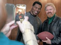 Herschel Walker has a photo taken with a Team Ramstein member at the Officer's Club on Ramstein Air Base, Jan. 9. Walker visited the Kaiserslautern Military Community to share his struggles and successes with his mental health while encouraging those he met to seek out help if they need it.