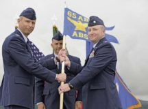 Col. Travis Leighton (left), 65th Air Base Group commander hands Lt. Col. Adam King the 65th Air Base Squadron guidon signifying the activation of the new squadron located at Lajes Field, Azores, Portugal, June 13. The 65th ABS consolidated the functions of the deactivated units 65th Operations Support Squadron, 65th Communications Squadron and the 65th Security Forces Squadron.