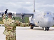 An Airman deployed with the 37th Airlift Squadron marshals a C-130J Super Hercules at Powidz Air Base, Poland, July 10.