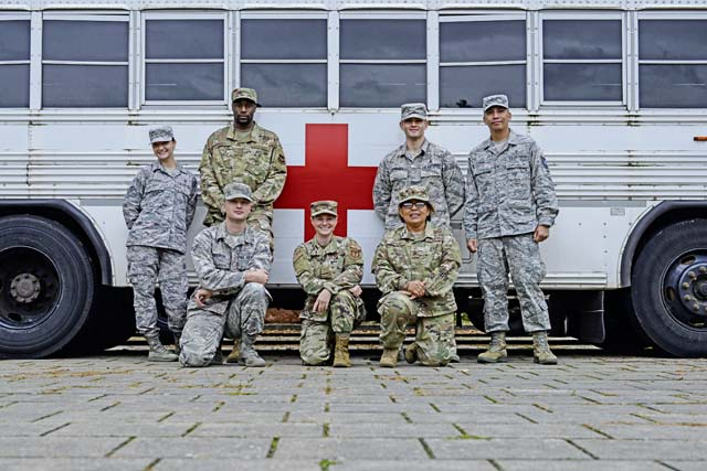 A group of U.S. Air Force service members from the 86th Aerospace Medicine Squadron pose in front of a medical transport shuttle at Ramstein Air Base, Oct. 9. The Airmen were part of a larger group that welcomed wounded warriors who visited the base a week before.