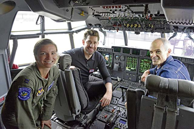 American actors John Krasinski and Michael Kelly sit in a cockpit with U.S. Air Force Capt. Korie Roberts, 37th Airlift Squadron instructor pilot, during a base tour on Ramstein Air Base,  Oct. 15.