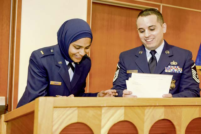 Second Lt. Saleha Jabeen, chaplain candidate, and Master Sgt. Alexander James, recruiter, sign recruitment paperwork after Jabeen's commissioning ceremony Dec. 18, 2019, at the Catholic Theological Union in Chicago. Jabeen is scheduled to continue training and be assigned to a unit once she has completed all initial training requirements.