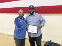 "Matthew Gilliard, Youth Sports Director presents a ""Certificate of Appreciation"" for doing an outstanding job in singing the National Anthem during the Opening ceremony to Derrick Alexander."