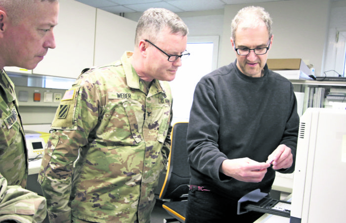 Col. Michael Weber and Command Sgt. Maj. Thurman Reynolds, Landstuhl Regional Medical Center command team, speak with Dr. Michael Koenig, technical supervisor, Virology Laboratory, to learn about LRMC's Centers for Disease Control and Prevention 2019-Novel Coronavirus Real-Time Reverse Transcriptase Diagnostic Panel, a CDC-developed laboratory test kit to detect 2019 novel coronavirus.