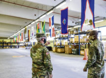 Brig. Gen. Gregory Brady, 10th Army Air and Missile Commanding General, talks with Chief Warrant Officer 3 Samuel Adeyame, a supply systems technician assigned to Echo Company 5th Battalion, 4th Air Defense Artillery Regiment at Smith Barracks, June 8. The flags in the background are displayed in the E Co. Supply Support Activity building to represent where soldiers of the company are originally from. Photo by Sgt. 1st Class Jason Epperson