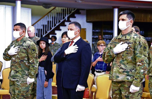 Tommy Mize, IMCOM-E director, center, stands with Col. Jason Edwards, outgoing USAG Rheinland-Pfalz commander, left, and Col. Vance Klosinski, new USAG Rheinland-Pfalz commander during the national anthem before the change of command ceremony July 22 in Kaiserslautern. Photos by Elisabeth Paque
