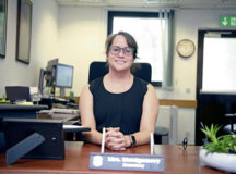 Jo Montgomery, 86th Mission Support Group commander's secretary, poses for a photo at her desk at Ramstein Air Base, July 28. As the daughter of parents belonging to the 82nd Airborne Division, Montgomery said she's proud to contribute to her family's rich history with the military.