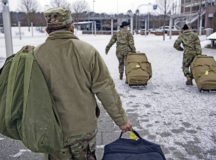 Members of the Deployment Transition Center carry the bags of redeployers at Ramstein Air Base, Germany Feb. 9, 2021. The DTC teaches redeployers about comprehensive fitness which consist of mental, social, physical and spiritual health. (U.S. Air Force photo by Staff Sgt. Kirby Turbak)