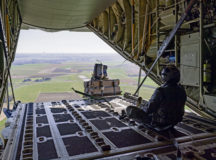 U.S. Air Force Senior Airman Kieran Durden, 37th Airlift Squadron loadmaster, releases cargo from the back of a C-130J Super Hercules aircraft over Chièvres Air Base, Belgium, March 29, 2021. A team of multi-capable Airmen (MCA) from Ramstein Air Base, Germany, exercised skillsets outside their career fields to support airdrop operations during a Cross-Functional Airlift Support Personnel (CASPER) training. (U.S. Air Force photo by Senior Airman John R. Wright)