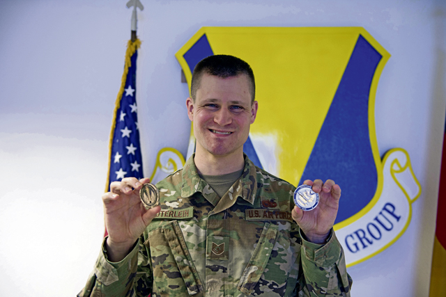 U.S. Air Force Tech. Sgt. Matthew Lauterlein, 86th Maintenance Group maintenance management analyst and non-commissioned officer in charge, shows coins received for being recognized as Airlifter of the Week at Ramstein Air Base, Germany, April 22, 2021. Lauterlein's implementation of Power BI has improved training and effectiveness while ensuring correct information is available for the 86th MXG and wing leadership. (U.S. Air Force photo by Airman 1st Class Manuel G. Zamora)
