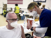 Andreas Heinze, 721st Aerial Port Squadron motor carrier safety specialist, receives a COVID-19 vaccine shot from Iris Geist, a German local national nurse, at Ramstein Air Base, Germany, April 29, 2021. This marks the first time local national members were able to volunteer to receive a COVID-19 vaccine from the installation. Ramstein is the first base in U.S. Air Forces in Europe to vaccinate its local national workforce. (U.S. Air Force photo by Senior Airman Milton Hamilton)