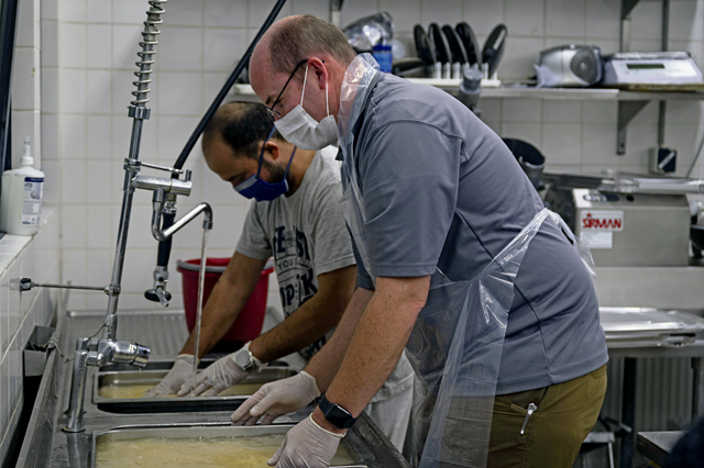 An evacuee, right, and Ben Furqueion, 86th Force Support Squadron business operations flight chief, left, wash rice during food prep at Ramstein Air Base, Germany, Sept. 13, 2021. The evacuees made a meal for the 786th Force Support Squadron and the 86th Force Support Squadron staff to demonstrate the kind of spices and ingredients used in a customary Afghan dish. Evacuees receive temporary lodging, food and water, and access to medical care at Ramstein while awaiting transportation to other transient locations. (U.S. Air Force photo by Senior Airman Milton Hamilton)